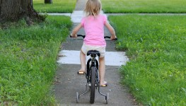 Girl_on_bike_training_wheels